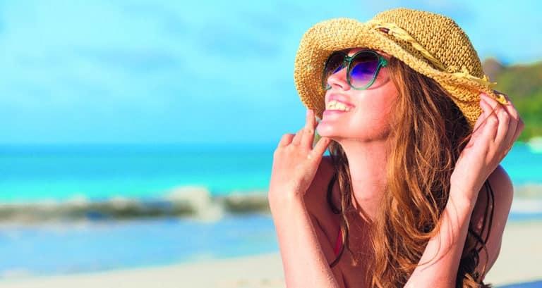 Woman,in,bikini,and,straw,hat,lying,on,tropical,beach